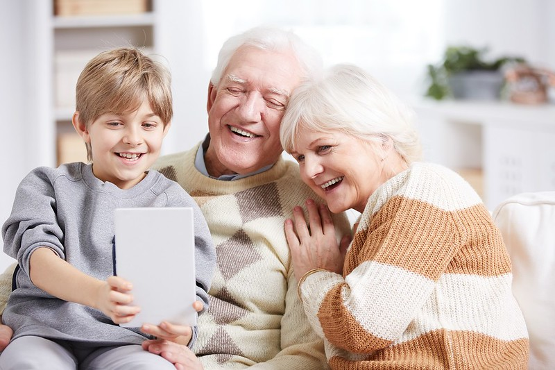Child showing tablet to his grandparents