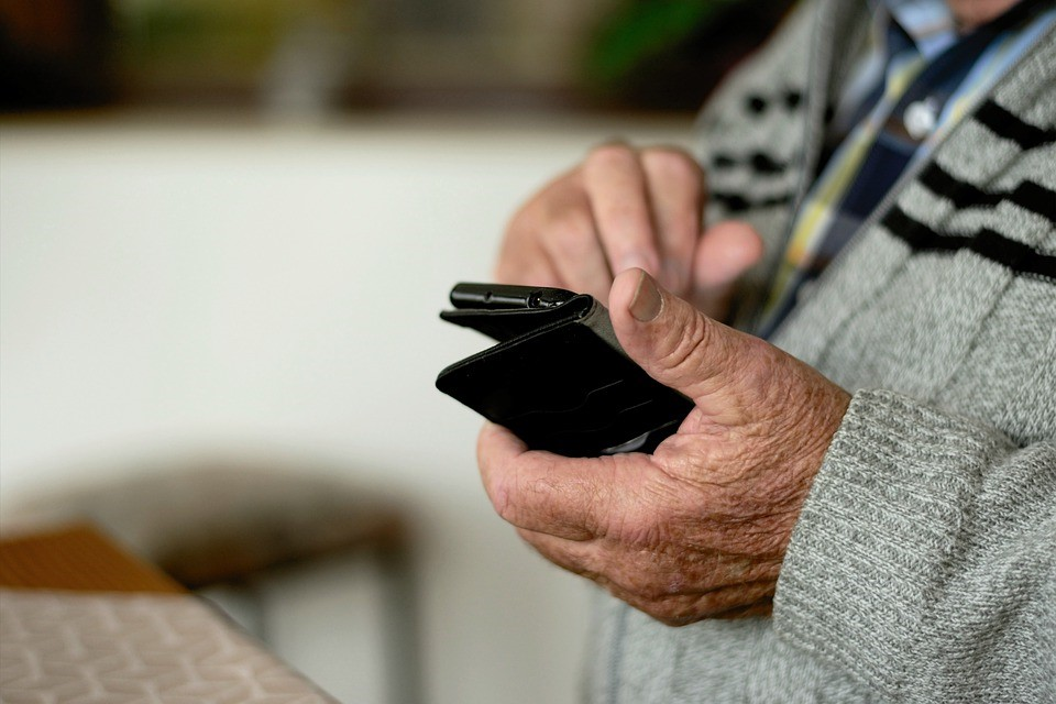 Grandparent holding latest mobile in hand